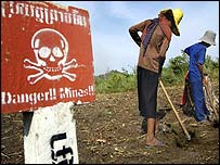Working a field next to a landmine warning sign on the Thai-Cambodia border