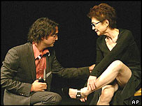 Yoko Ono sits on stage as her son Sean cuts off a piece of her tunic