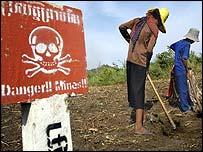 Agricultores trabajan la tierra en la frontera entre Camboya y Tailandia cerca de un aviso que indica la presencia de minas en la zona.