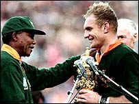 Francois Pienaar receives the Webb Ellis trophy from former President Nelson Mandela