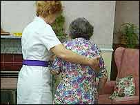 An elderly lady is helped to her chair