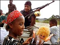 Girl alongside government forces outside Monrovia plays with doll