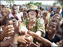 An Australian soldier (C) gives out sweets to children in Auki, the capital of Malaita