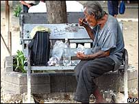 A Thai homeless man eats his lunch while sitting on a road-side bench in Bangkok