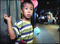 A young Thai boy begs for money as others pass by on Sukhumvit Road