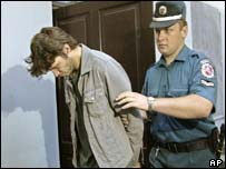 A police officer escorts French rock star Bertrand Cantat