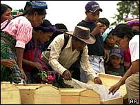 Guatemalans inspect remains of war victims exhumed  from a mass grave