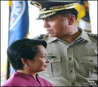Philippine President Gloria Arroyo (L) is accompanied by armed forces chief General Narciso Abaya (R)