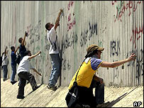 Activists spray graffiti on the security fence in the West Bank town of Qalqilya, 31 July 2003