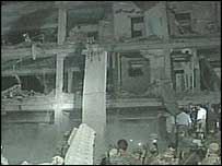 Rescue workers gather around the shell of the building