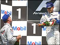 David Coulthard celebrates on the German GP podium with Juan Pablo Montoya