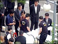 El cuerpo de Chung Mong-hun es movilizado por agentes policiales.