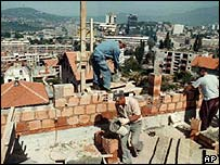 Workers repair a house in Sarajevo