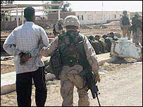US soldier leads away Iraqi prisoner at Abu Ghraib