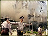 Indonesian police officers try to push journalists away from the site of an explosion at the Marriott Hotel in Jakarta