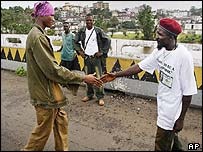 A rebel and a government fighter shake hands on a bridge