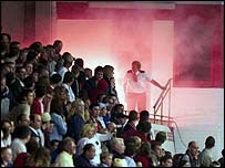 Fans in the main stand are illuminated by the flare