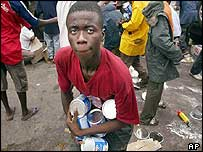 Boy stealing tins of food from Monrovia's port