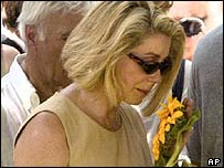 Actress Catherine Deneuve with a flower at the cemetery