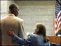 Kobe Bryant is patted on the back by his lawyer in the Eagle court room