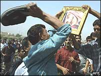 An Iraqi hits a picture of former King Hussein with his shoe