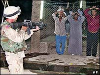 Soldier guards Iraqis during raid