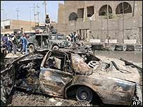 A burned vehicle sits outside the Jordanian embassy, 7 August 2003