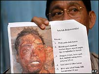 Chief of detectives Erwin Mappaseng holds up a sketch of the severed head