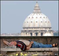 A man sleeps in front of St Peter's Basilica in Rome