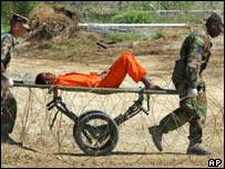 A detainee from Afghanistan is carried on a stretcher before being interrogated by military officials at Guantanamo Bay, Cuba