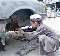 Boy repairs axle in Pakistani city of Peshawar