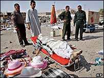 Iraqi policemen look at the body of a suspected gun dealer who was killed by US soldiers at a market in Tikrit, 8 August 2003