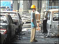 A worker stands among cars wrecked in the hotel blast