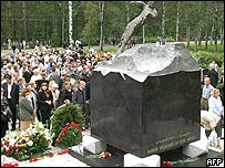 The memorial is a black granite block surrounded by flower-strewn gravestones for the 32 sailors who are buried there