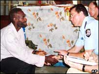 Harold Keke shakes hands with Assistant Commissioner of the Royal Solomon Islands Police Ben McDevitt in Mbiti, Guadalcanal