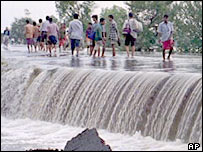 Villagers crossing flooded river in Assam
