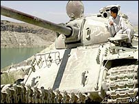 Afghan man sitting atop damaged tank