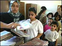 Iraqi teacher hands out books