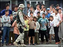 Iraqi children talk to a US soldier as he stands guard during the opening ceremony of a police station 