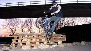 A street rider balances on one of his pegs to perform an icepick