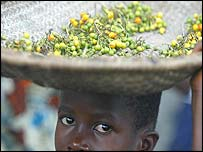 Liberian child carrying grain