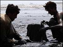 Man collecting oil from Karachi beech