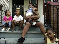 Patricia Sykes sits with her grandchildren on her front porch to stay cool during the power cut in Detroit