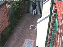 A person tries to open the gate to a property