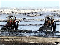 Pakistani workers use tractors to scrape oil off a beach after the Tasman Spirit ran aground