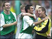 Hibs players celebrate victory as fans invade the pitch