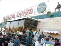 Israeli Police and forensics experts stand outside the Maxim restaurant, Haifa, 4 October 2003