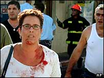 Woman covered in blood at the scene of a suicide bombing in the northern Israeli city of Haifa, 4 October 2003