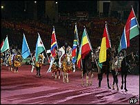 Riders carry the national flags into the stadium