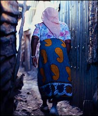 Woman walking in a slum (Image: UN Habitat)